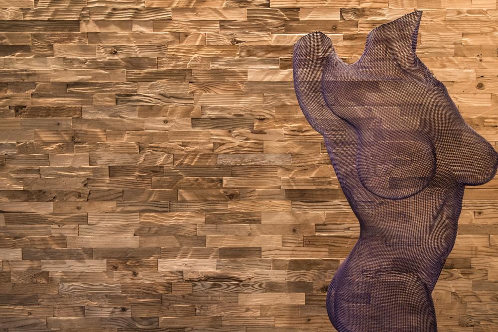 Holzwand und Torso-Plastik
